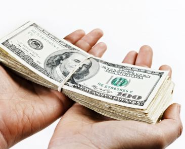 A pair of hands holds out a large bundle of US dollars. Isolated on white.