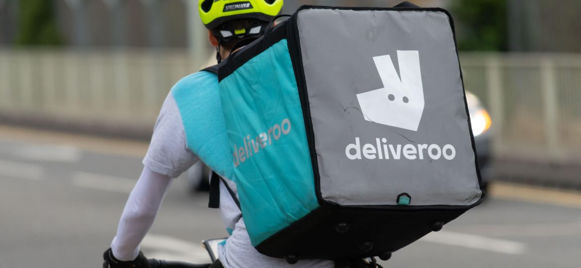 A Deliveroo fast food delivery driver seen on a push bike in Cardiff, Wales, UK.